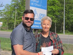 Pati Habermann, Staff Representative assigned to OPSEU Local 294, presents a cheque from OPSSU to local president, Chris Terreberry.